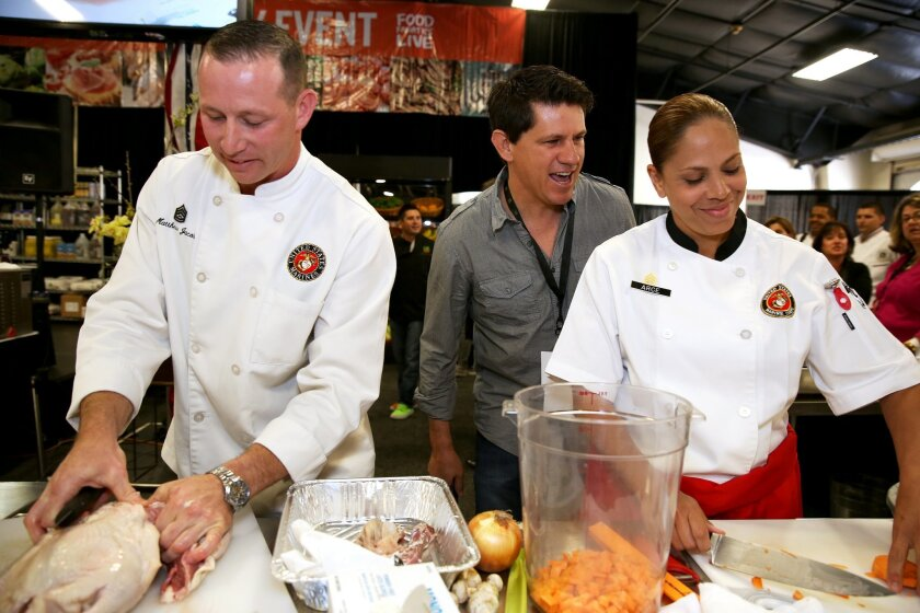 Gunnery Sgt. Matthew Jacobs and Staff Sgt. Karla Arce prepare their meal while Food Network judge Troy Johnson looks on the Boiling Points competition at the Del Mar Fairgrounds April 16. The Marine team took 1st place. Photo by Gunnery Sgt. Leo Salinas