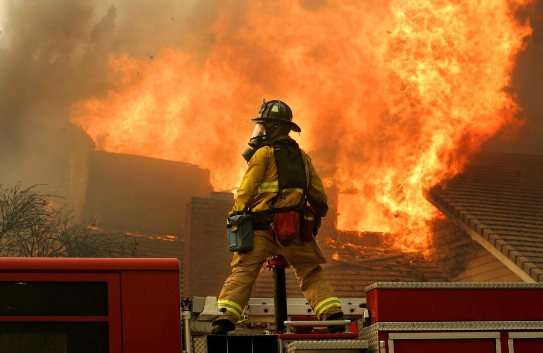 A San Diego firefighter battles a blaze in Rancho Bernardo during a firestorm on Monday, October 22, 2007.
