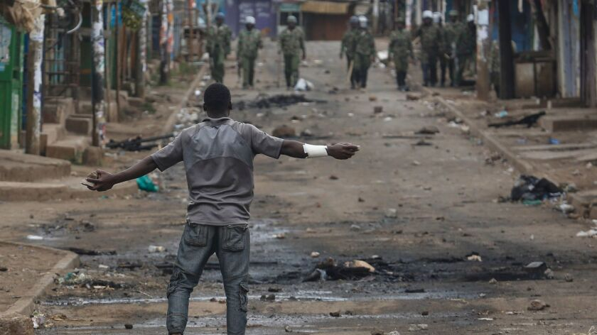 A supporter of the opposition leader Raila Odinga faces off against police officers during a protest in the Kibera area of Nairobi, Kenya, on Saturday.