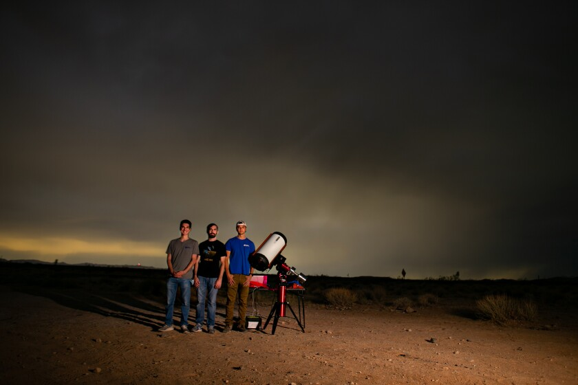 Three people stand in the desert with a telescope  -  url https 3A 2F 2Fcalifornia times brightspot - How making satellites self-destruct can help clean up space