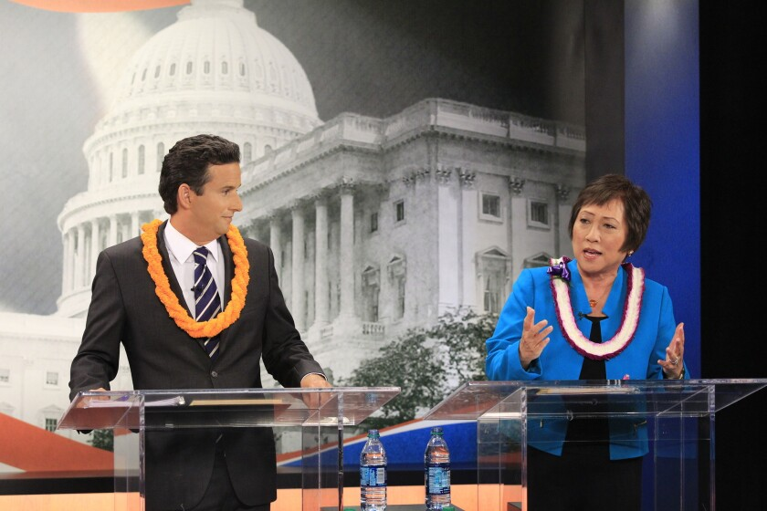 U.S. Sen. Brian Schatz, left, listens as Rep. Colleen Hanabusa answers a question during a debate in July.