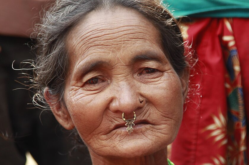 Sukhmaya Jamang, 60, waits for international aid to be unloaded in the destroyed village of Balua, near the epicenter of Saturday's massive earthquake, in the Gorkha District of Nepal, Thursday, April 30, 2015. (AP Photo/Wally Santana)