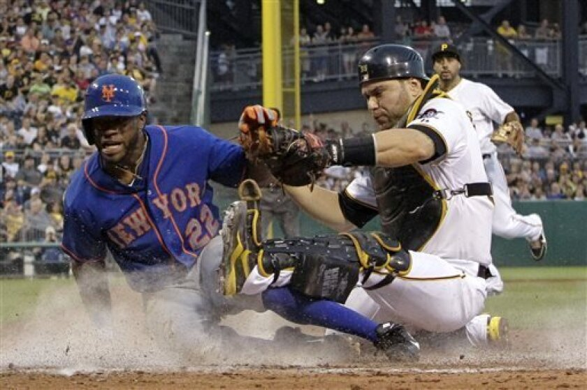 Pittsburgh Pirates catcher Russell Martin (55) holds on to the ball after tagging out New York Mets' Eric Young Jr. (22), who attempted to score from third on an infield grounder by David Wright to third baseman Pedro Alvarez, right rear, during the fifth inning of a baseball game in Pittsburgh on Saturday, July 13, 2013. (AP Photo/Gene J. Puskar)