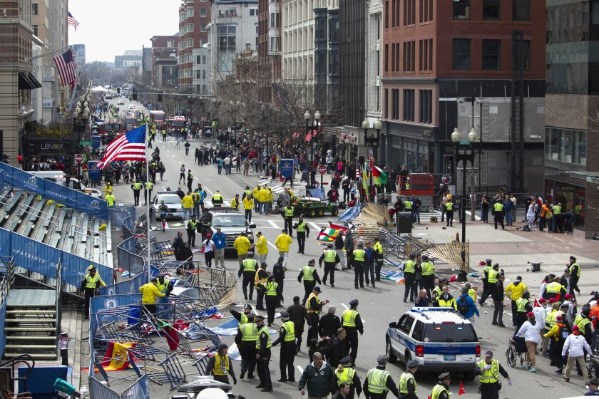 First responders rush to where two explosions occurred along the final stretch of the Boston Marathon on Boylston Street.