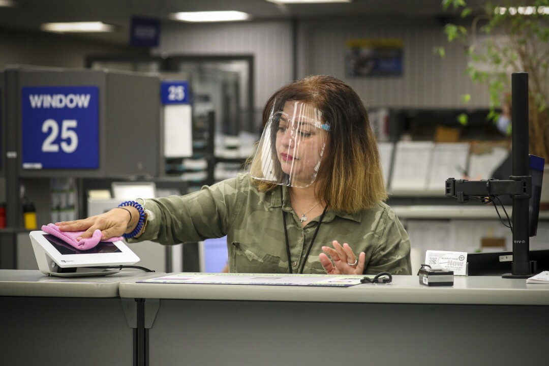 A DMV worker wearing a transparent plastic face shield wipes down an electronic terminal at her workstation