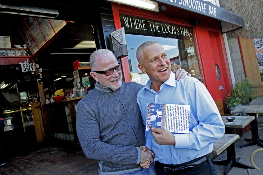 City Council District 11 candidate Mike Bonin, right, is seen shaking hands with Clabe Hartley, owner of the Cow's End in Venice.
