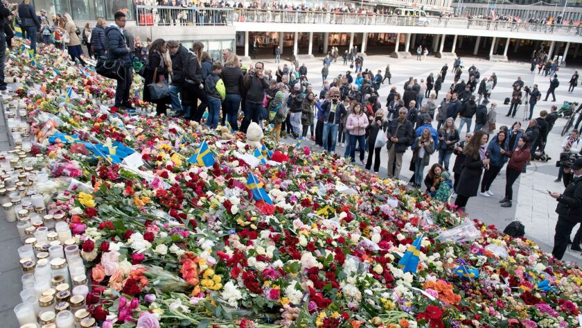 People leave flowers on the steps at Sergels Torg following Friday's attack in central Stockholm, Sw
