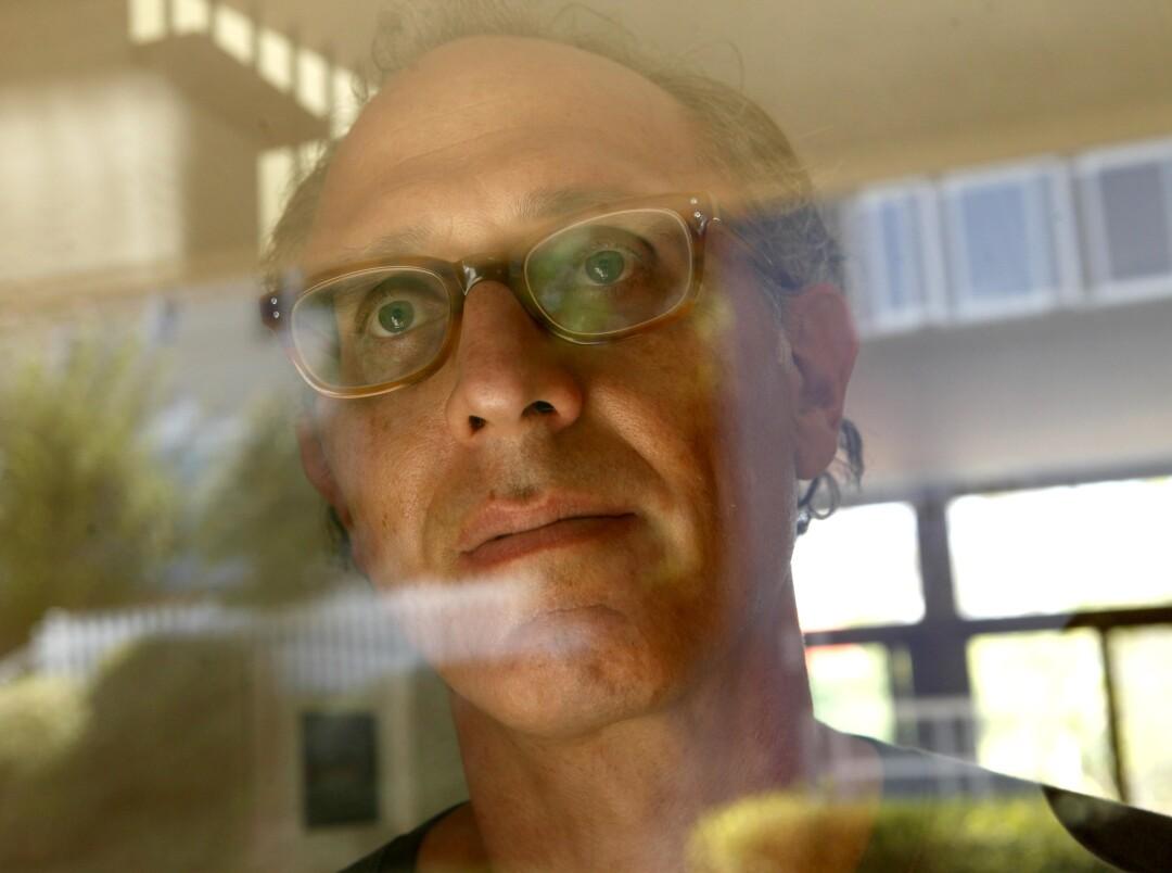 A man stares through a window