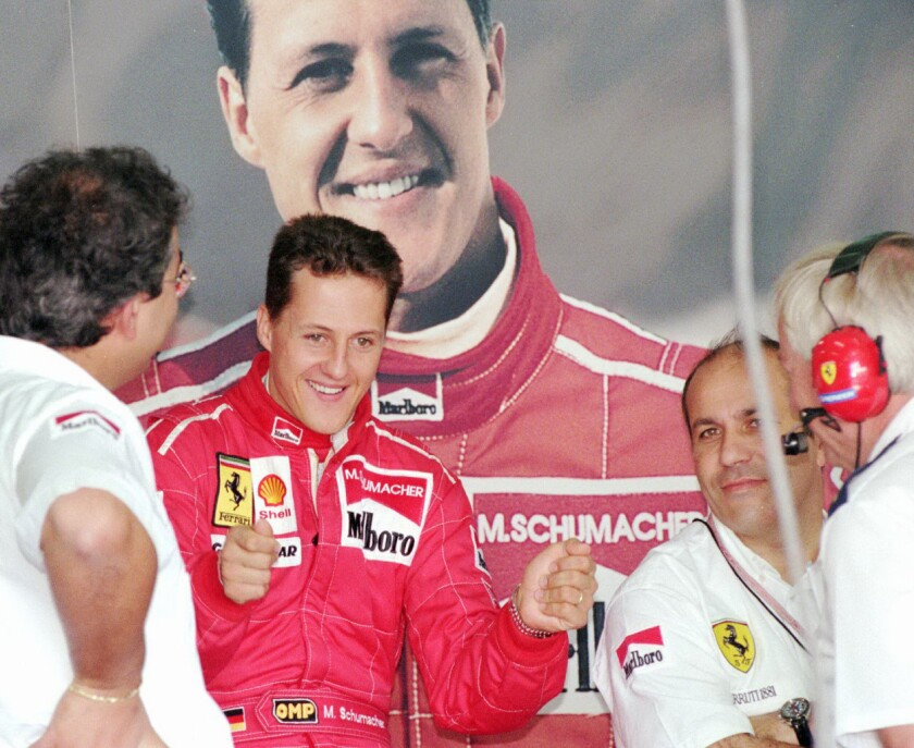 German Formula One driver Michael Schumacher jokes with Ferrari mechanics in front of a large photo of himself during the first day of testing after the Portuguese Grand prix at Estoril Tuesday, September 24, 1996.