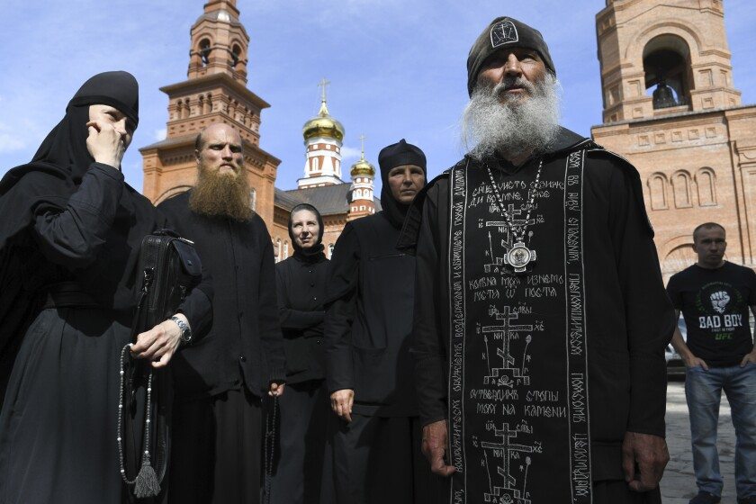 Father Sergiy, a Russian monk who has defied the Russian Orthodox Church's leadership, right, speaks to journalists in Russian Ural's Sredneuralsk, Russia, Wednesday, June 17, 2020. The monk, who has denied the coronavirus' existence and urged believers to ignore the Kremlin's lockdown orders, has taken control of a monastery in the Ural Mountains. (AP Photo/Vladimir Podoksyonov)