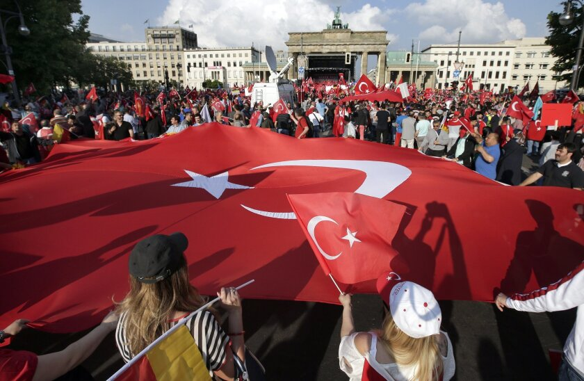 Protesters hold a giant flag of Turkey in front of the Brandenburg gate in Berlin, Germany, Wednesday, June 1, 2016, as they demonstrate against a resolution of the German federal parliament, Bundestag, on the Armenian Genocide a century ago. Turkey's relations with Germany will be harmed if the pa