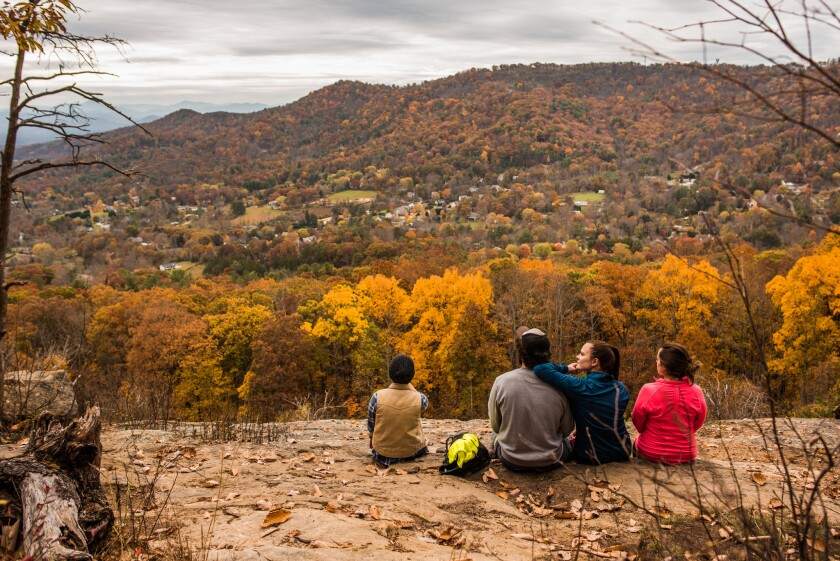 Laura Connor, center right, takes in the view of the Haw Creek Valley with her family along the Blue Ridge Parkway near Asheville, N.C.