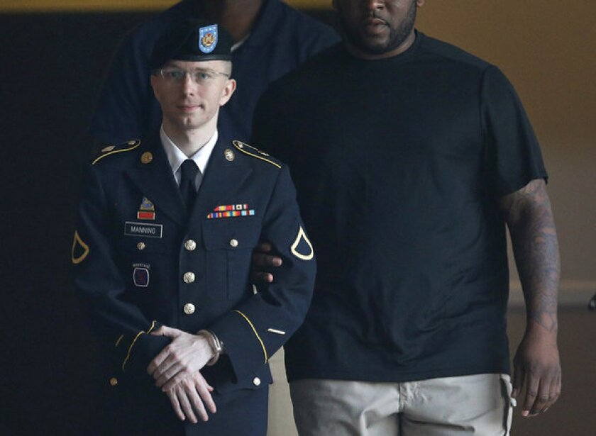 Army Pfc. Bradley Manning is escorted to a waiting security vehicle outside of a courthouse in Fort Meade, Md. after appearing for a hearing at his court martial.