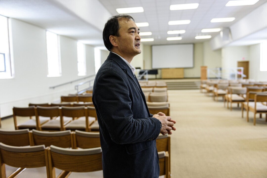 The Rev. Yuanlai Zhang stands in front of rows of chairs at his church