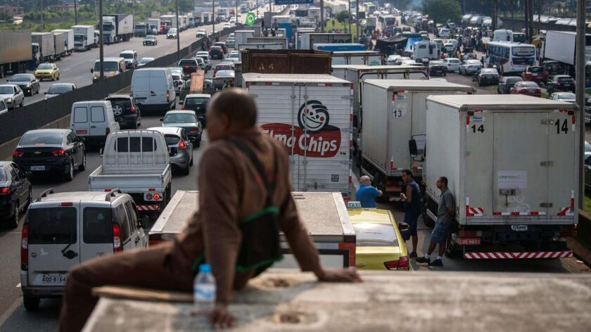 Brazilian truck drivers on Friday partially block a road in Duque de Caxias, a city near Rio de Janeiro, during the fifth day of their nationwide strike to protest rising fuel costs.