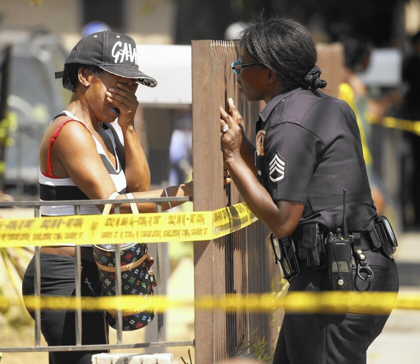 LAPD Sgt Emada Tingirides, right, talks to the sister of a homicide victim.
