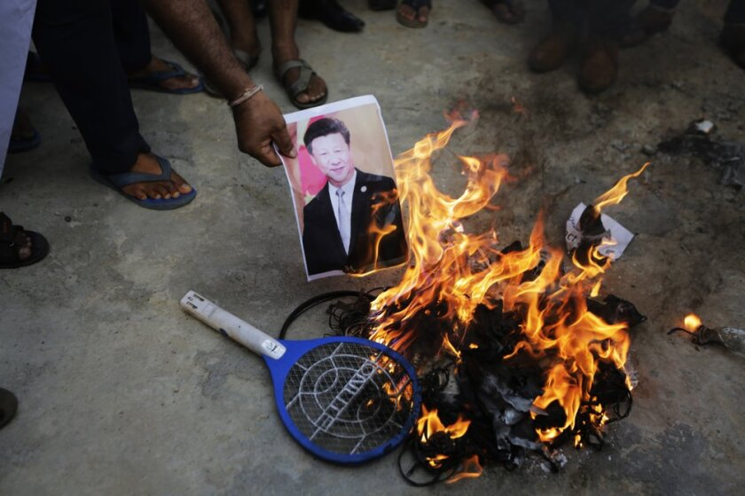 An Indian man burns a photograph of Chinese president Xi Jinping