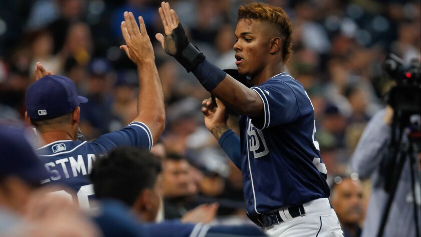 Padres outfield prospect Jeisson Rosario receives congratulatory high-fives in the dugout in a game against Texas Rangers minor leaguers on Saturday, Sept. 30, 2017, at Petco Park.