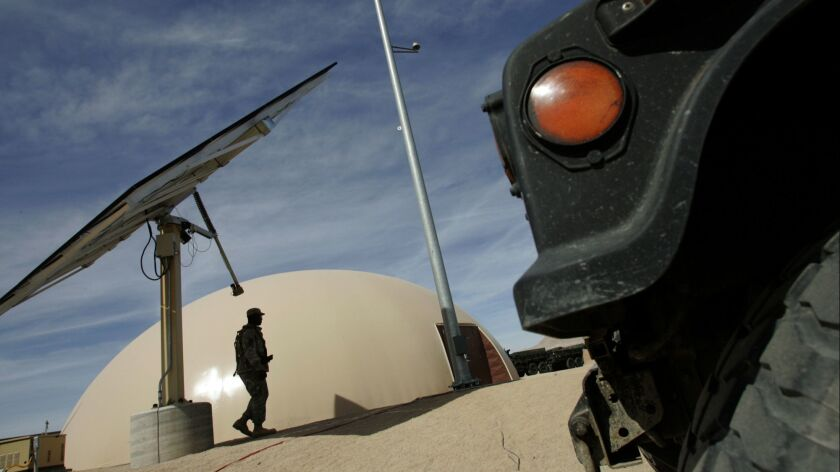 A soldier walks past solar panels at Fort Irwin in the Mojave desert in 2009.