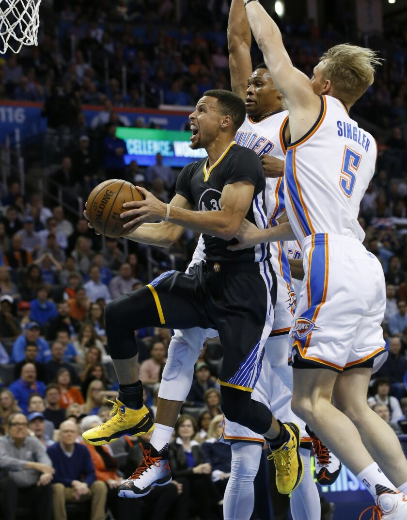 Golden State Warriors guard Stephen Curry, left, goes up for a shot in front of Oklahoma City Thunder forward Kevin Durant, center, and forward Kyle Singler (5) during the first quarter of an NBA basketball game in Oklahoma City, Saturday, Feb. 27, 2016. (AP Photo/Sue Ogrocki)
