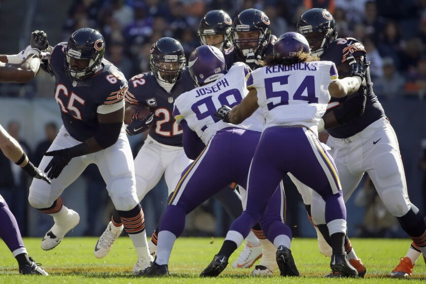 Chicago Bears running back Matt Forte (22) looks for a hole as he rushes against the Minnesota Vikings runs the ball during the first half of an NFL football game Sunday, Nov. 1, 2015, in Chicago. Defending are Minnesota Vikings defensive tackle Linval Joseph (98) and  linebacker Eric Kendricks (54