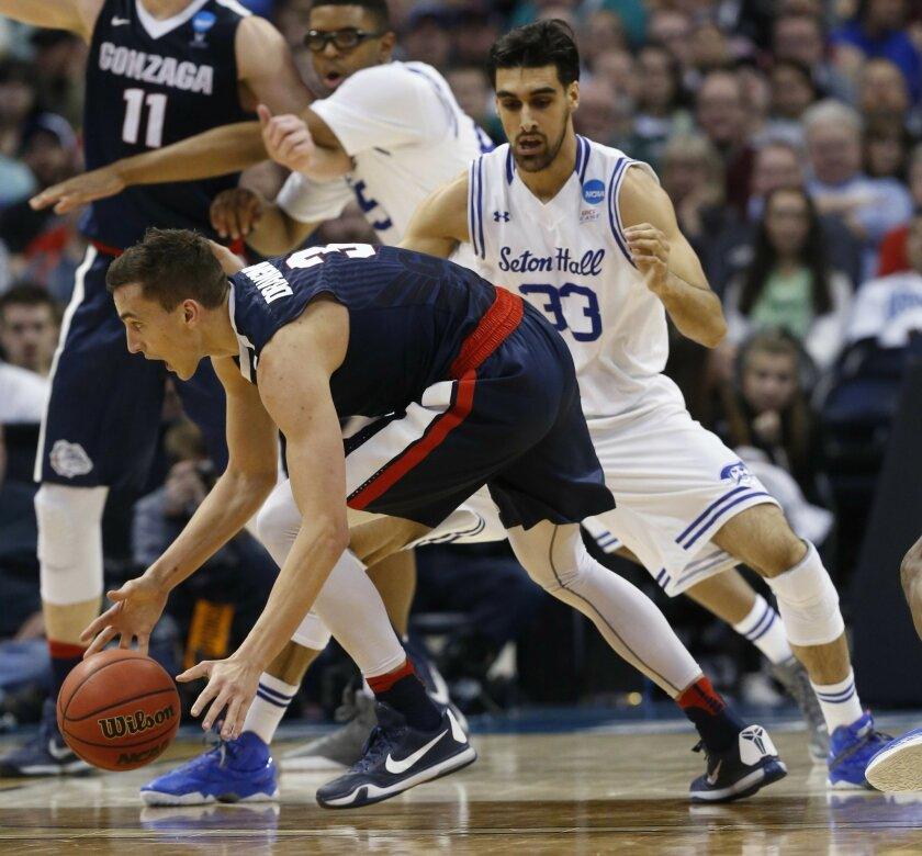 Gonzaga guard Kyle Dranginis, front, scoops up a loose ball as Seton Hall forward Veer Singh defends during the first half of a first-round game Thursday, March 17, 2016, in the NCAA men's college basketball tournament in Denver. (AP Photo/Brennan Linsley)