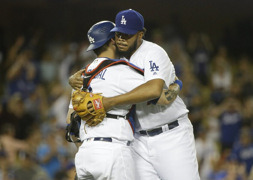 Los Angeles Dodgers relief pitcher Kenley Jansen, right, and catcher Yasmani Grandal celebrate the team's 4-1 win against the Washington Nationals in a baseball game, Monday, June 20, 2016, in Los Angeles. (AP Photo/Jae C. Hong)
