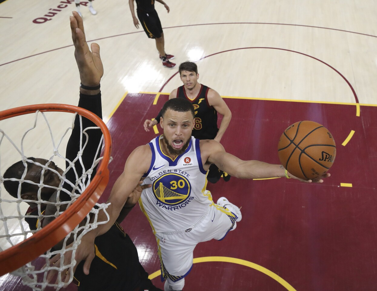 Golden State Warriors' Stephen Curry shoots against Cleveland Cavaliers' LeBron James during the second half of Game 4 of basketball's NBA Finals, Friday, June 8, 2018, in Cleveland. The Warriors defeated the Cavaliers 108-85. (Kyle Terada/Pool Photo via AP)