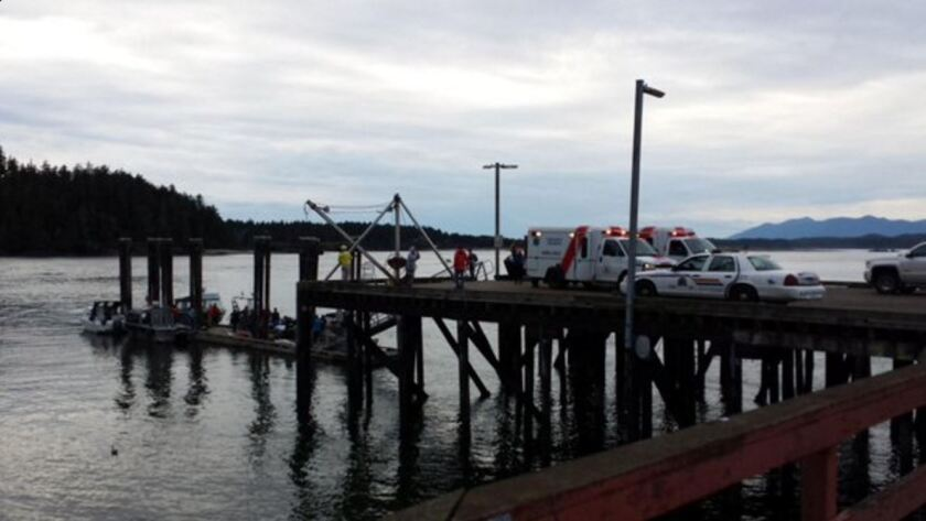 Emergency vehicles gather on a pier in Tofino, Canada, on Sunday after a whale-watching boat sank.
