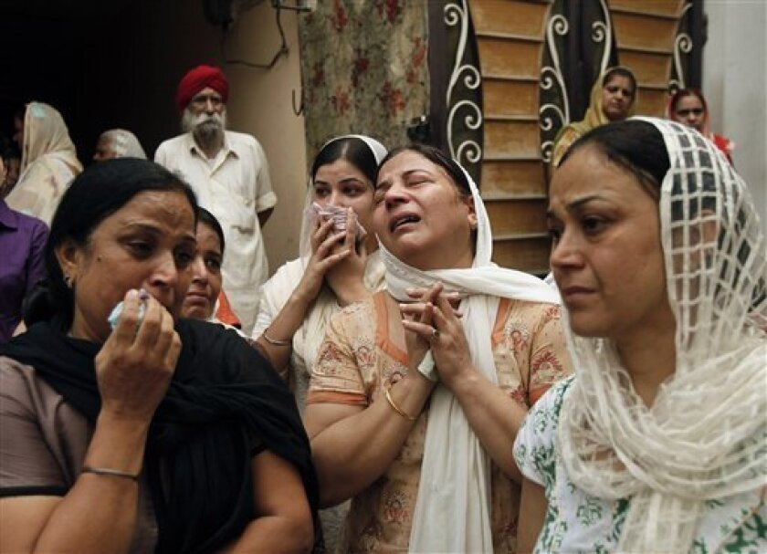 Relatives of blast victim Inder Singh mourn as his body is taken for its funeral in New Delhi, India, Thursday, Sept. 8, 2011. Indian authorities detained three men for questioning Thursday as they scrambled for leads into a powerful briefcase bomb that tore through the crowds outside a New Delhi courthouse. (AP Photo/Gurinder Osan)