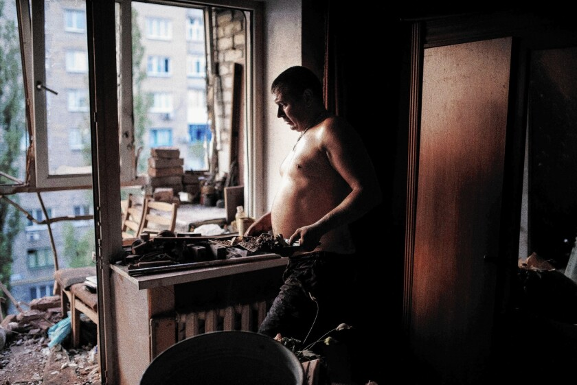 A man cleans up his damaged apartment after shelling in the Ukrainian town of Yasynuvata near the separatist stronghold of Donetsk on Aug. 12.