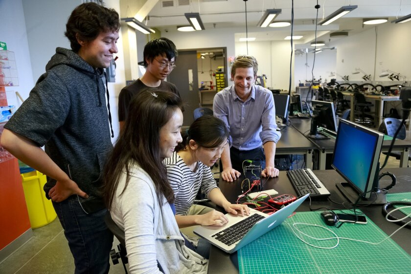 Computer science undergrad Yuhan Dai (leaning over laptop) shows her programming code to Jesse Dewald (facing front), staff director of UC San Diego's EnVision Maker Studio. Sainan Liu (seated), Jorge Garza (left) and Felix Zhong look on. / photo by Nelvin C. Cepeda * U-T