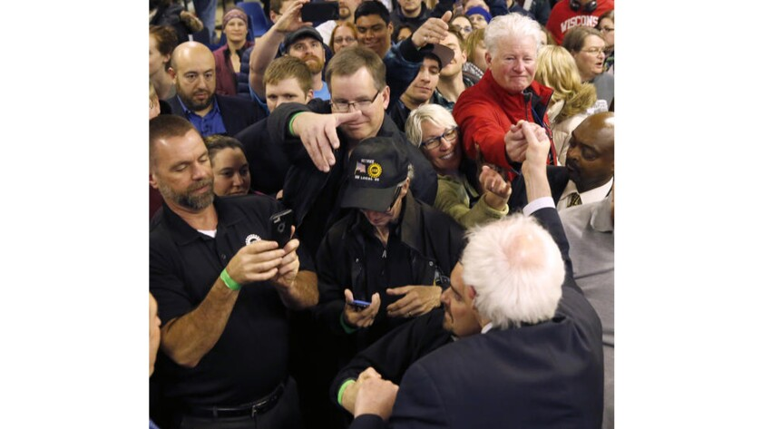 Democratic presidential candidate Sen. Bernie Sanders is mobbed by supporters at a rally at a union hall in Janesville, Wis., on April 4, 2016.