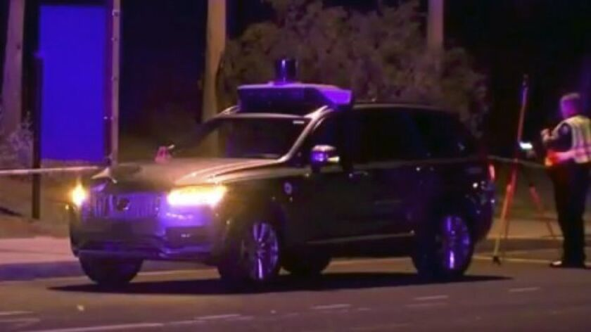 An investigator at the scene of a fatal accident involving a self-driving Uber vehicle in Tempe, Ariz.