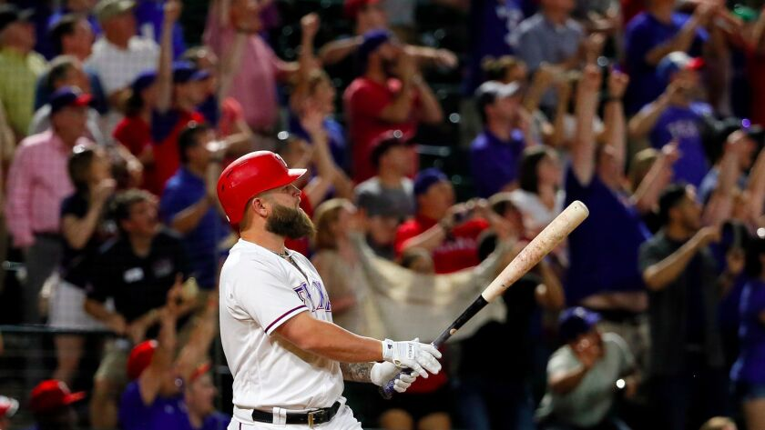 Fans stand and cheer as Texas Rangers' Mike Napoli watches his game-winning three-run home run off a
