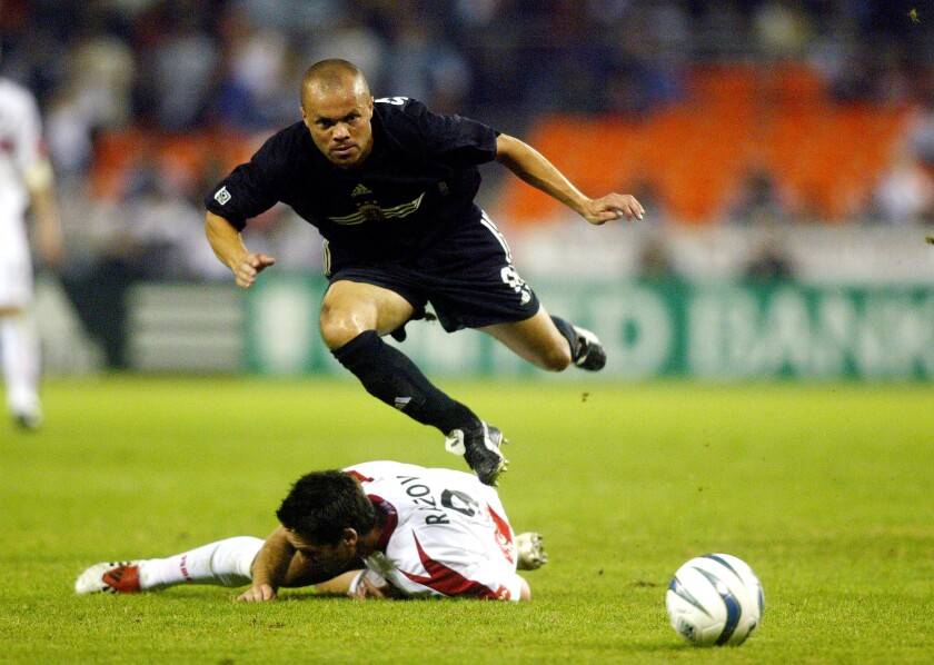 File-This Nov. 1, 2003, file photo shows DC United midfielder Earnie Stewart jumping over a slide tackle by Chicago Fire forward Ante Razov in the first half of an MLS soocer match in Washington. The three-time World Cup veteran Stewart has been hired as general manager of the U.S. men's national soccer team, a new position created after the Americans failed to qualify for this year's tournament. The U.S. Soccer Federation said Wednesday the 49-year-old will start work Aug. 1.