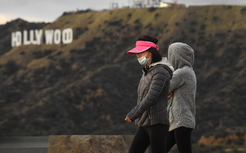 Hikers wearing masks because of the coronavirus walk past the Hollywood sign in Griffith Park.