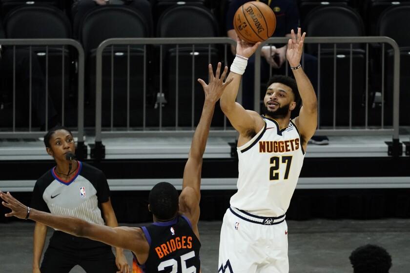 Denver Nuggets guard Jamal Murray shoots over Phoenix Suns forward Mikal Bridges (25) during the first half of an NBA basketball game Saturday, Jan. 23, 2021, in Phoenix. (AP Photo/Rick Scuteri)