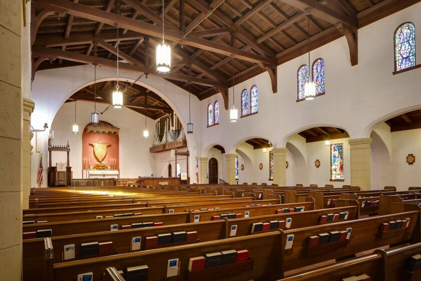 The interior of St. James By-the-Sea Episcopal Church in La Jolla features a high wooden ceiling, arches, columns and stained glass.
