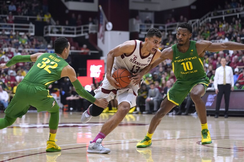 Stanford's Oscar da Silva, who had a career-high 27 points and added 15 rebounds, drives against Oregon's Anthony Mathis, left, and Shakur Juiston.