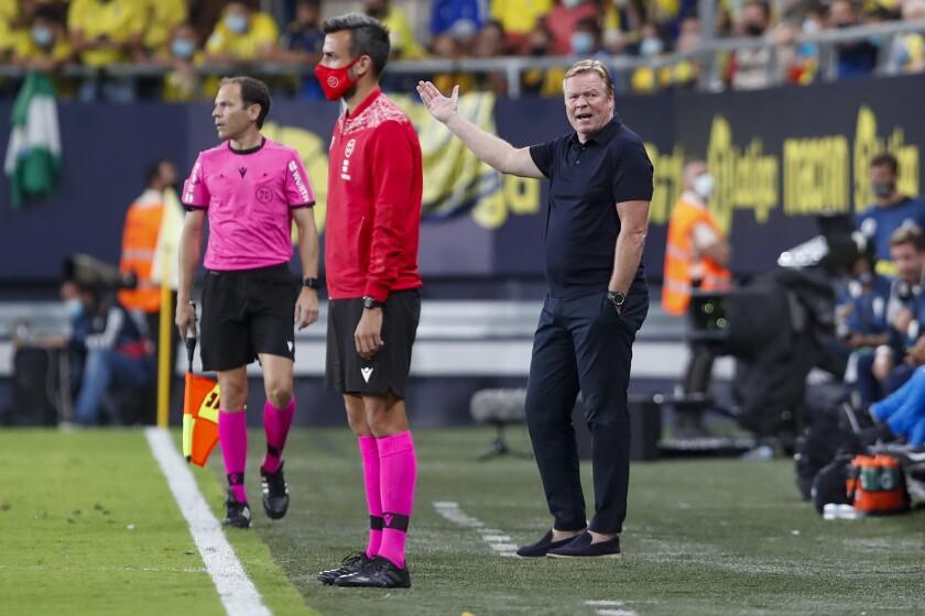 El técnico del Barcelona, Ronald Koeman, lanza quejas al cuatro árbitro durante el partido por la Liga ante el Cádiz, en el estadio Nuevo Mirandilla de Cádiz, España, el jueves 23 de septiembre de 2021. (AP Foto/Miguel Morenatti)