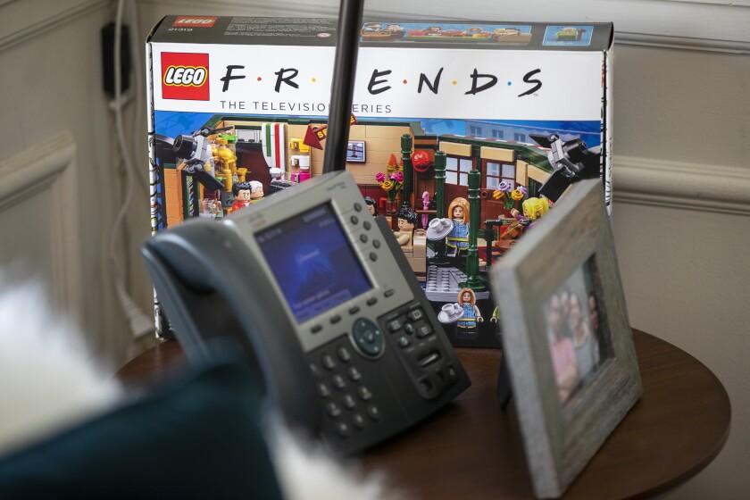 "A ""Friends"" Lego set, landline phone and framed photo on Marta Kauffman's desk."