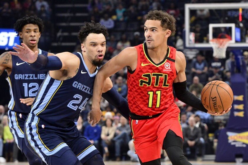 FILE - In this March 7, 2020, file photo, Atlanta Hawks guard Trae Young (11) handles the ball against Memphis Grizzlies guard Dillon Brooks (24) in the first half of an NBA basketball game in Memphis, Tenn. Lloyd Pierce sees improvement in the five players he calls the core of the rebuilding Atlanta Hawks. The coach knows he needs to deliver proof of that improvement next season. There was no proof in the standings of improvement in this shortened season despite the emergence of guard Trae Young as an All-Star in only his second season. (AP Photo/Brandon Dill, File)
