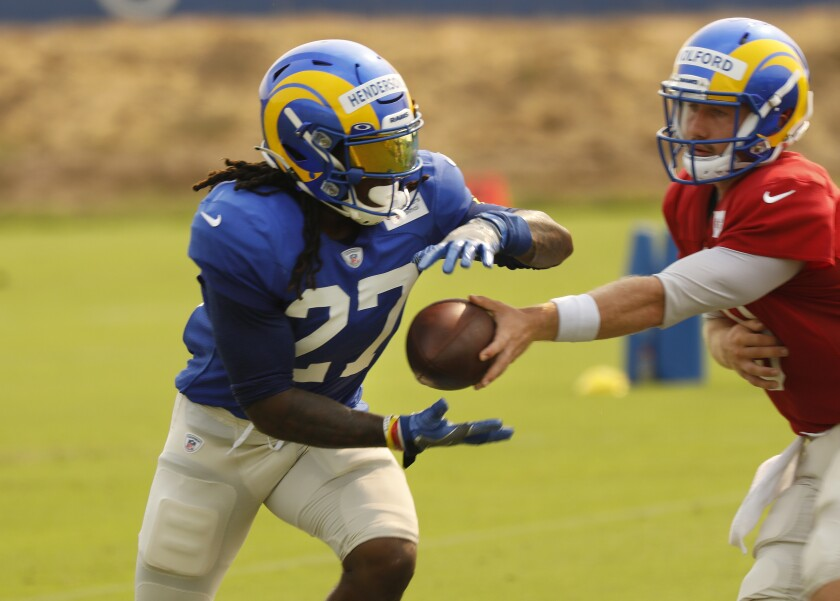 Rams running back Darrell Henderson takes a handoff during practice.