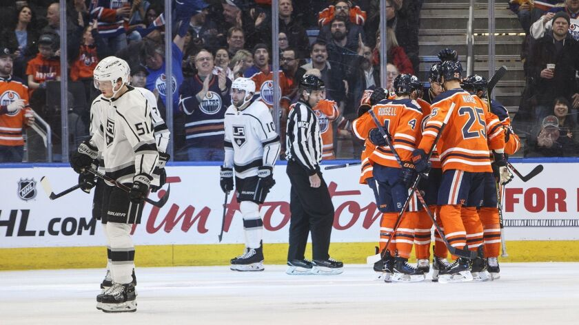 Kings' Austin Wagner (51) and Michael Amadio (10) skate past as the Edmonton Oilers celebrate a goal during the first period on Tuesday.