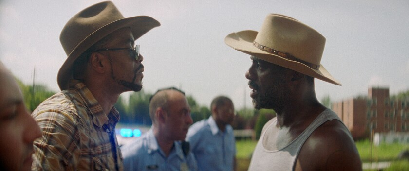 """Cliff """"Method Man"""" Smith and Idris Elba, wearing cowboy hats, look at each other"""