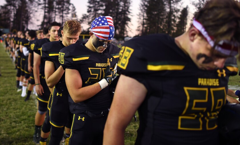 Lukas Hartley, second from right, bows his head with teammates during a moment of silence for the 86 victims of the Camp Fire.