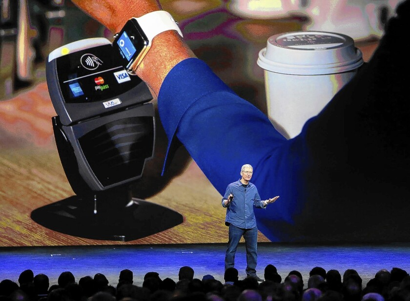 Apple Chief Executive Tim Cook shows how the Apple Watch can use Apple Pay to make purchases during a presentation Tuesday in Cupertino, Calif.