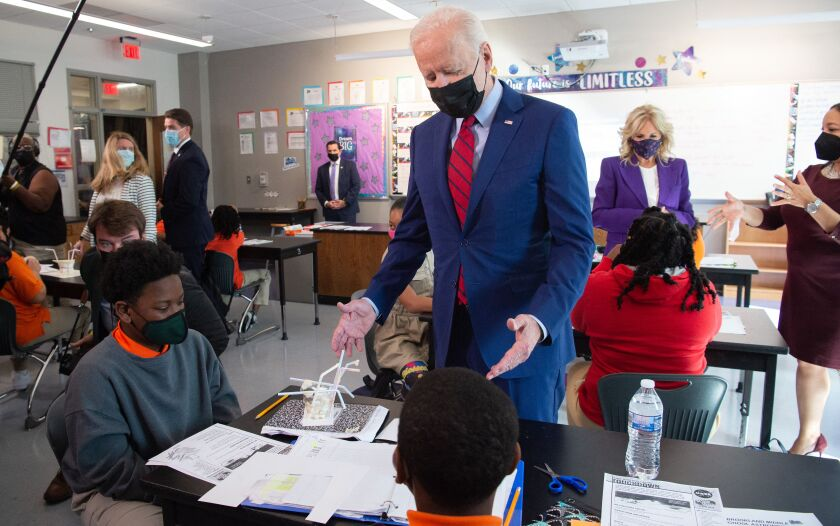 President Biden stands next to students working at a desk in a classroom