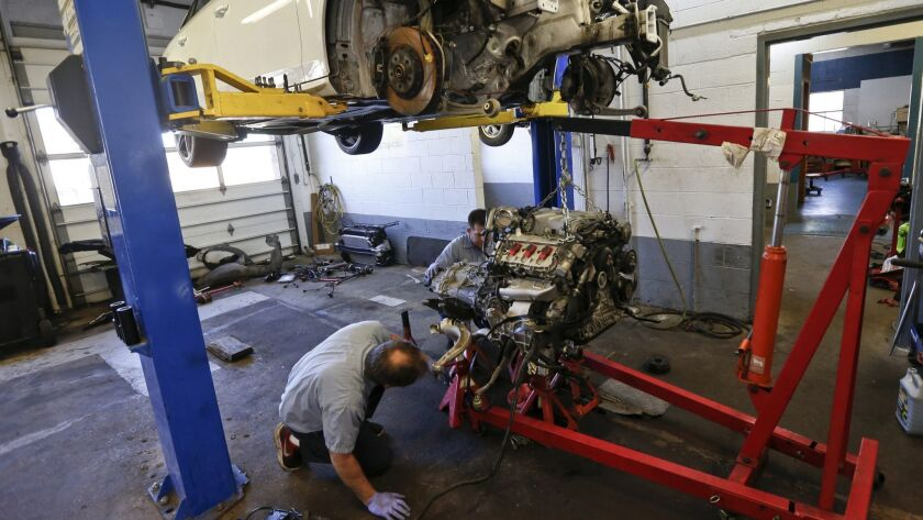 Automotive technicians Don Dimond, left, and Bernie Rabinovitz prepare to separate an engine and transmission assembly at a repair shop in Harmony, Pa. The average age of cars and trucks in the U.S. has hit a record 11.8 years.